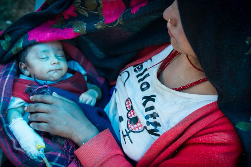 A mother holds her baby as IsraAID's medical tream provide urgent care. (Photo: Mickey Noam-Alon/IsraAID)