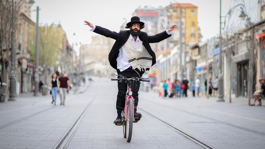 An ultr aorthodox Jewish man rides his bicycle along Jaffa Street in Jerusalem on APril 17, 2015. Photo by Mendy Hechtman/FLASH90