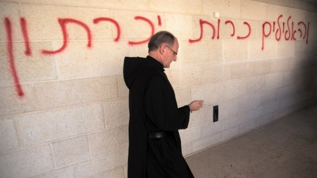 """A priest walks past graffiti reading in Hebrew, """"false idols will be eliminated,"""" as he inspects the damage at the Church of the Multiplication at Tabgha, on the shores of the Sea of Galilee in northern Israel, June 18, 2015. (AFP/Menahem Kahana)"""