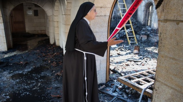 A nun inspects the damage at the Church of the Multiplication at Tabgha, on the shores of the Sea of Galilee in northern Israel, June 18, 2015. (AFP Photo/Menahem Kahana)