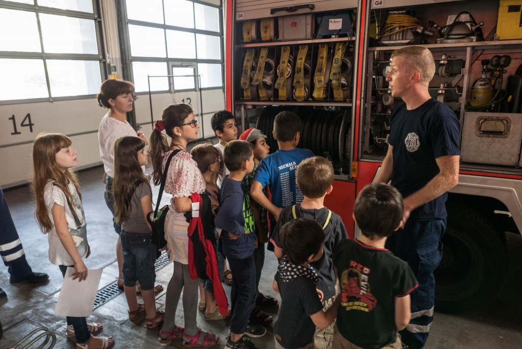 A Berlin fireman speaking to refugee children, September 2015. (Judith Kessler)