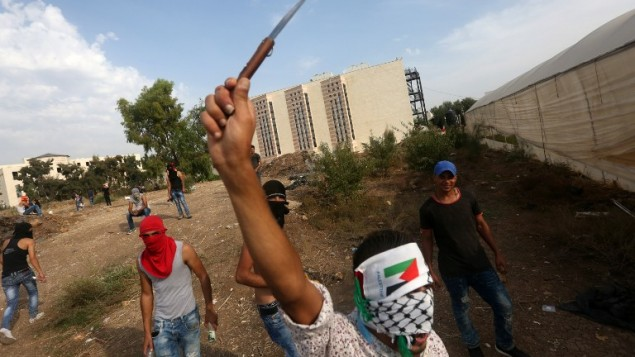 A Palestinian youth raises a knife during clashes with Israeli security forces (unseen) in the West Bank city of Tulkarem on October 18, 2015. (AFP/JAAFAR ASHTIYEH)