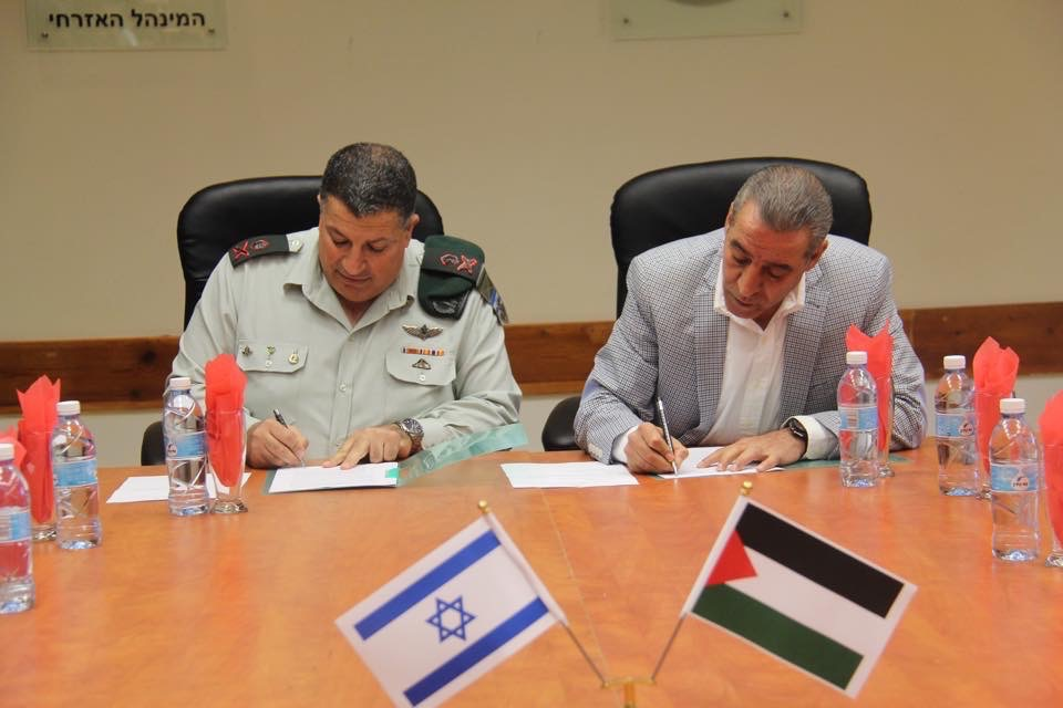 Maj. Gen. Yoav (Poli) Mordechai and Palestinian Civil Affairs Minister Hussein Al-Sheikh sign a memorandum of understanding to develop cellular service