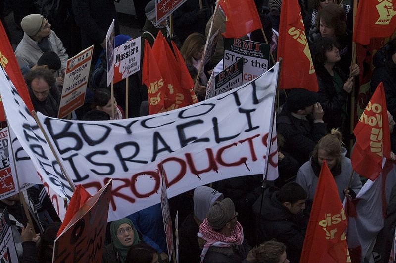 "BDS supporters protesting in London. The poster reads, ""Boycott Israeli Products"". (Wikipedia)"