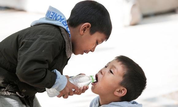 Migrant children sharing water