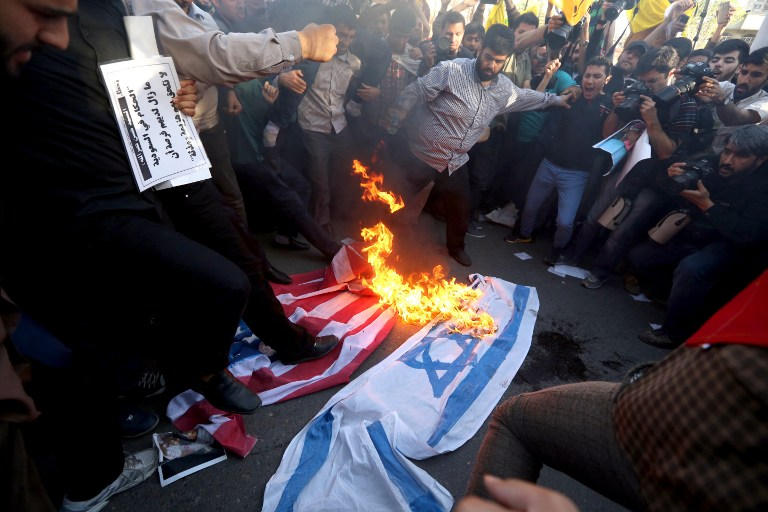 Iranians burn and stomp on Israeli and American flags during demonstration against the Saudi-led coalition's Operation Decisive Storm against the Huthi rebels in Yemen, outside the Saudi embassy in Tehran on April 13, 2015. AFP PHOTO/ATTA KENARE