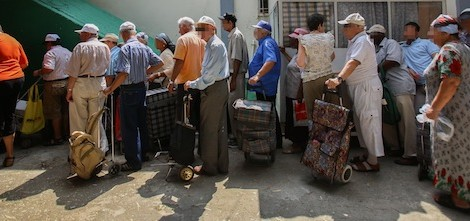People waiting in line for food packages at a distribution center for needy in Lud on September 11, 2012, ahead of the Jewish holiday of Rosh Hashanah. Photo by Yonatan Sindel / Flash90