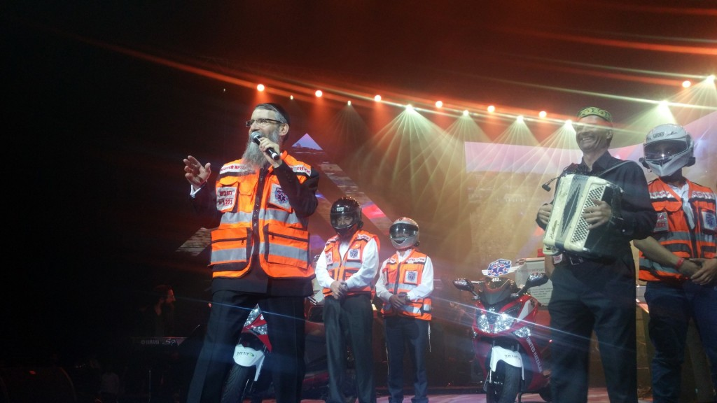 Avraham Fried dons a United Hatzalah vest and performs for the gathered volunteers and their families.