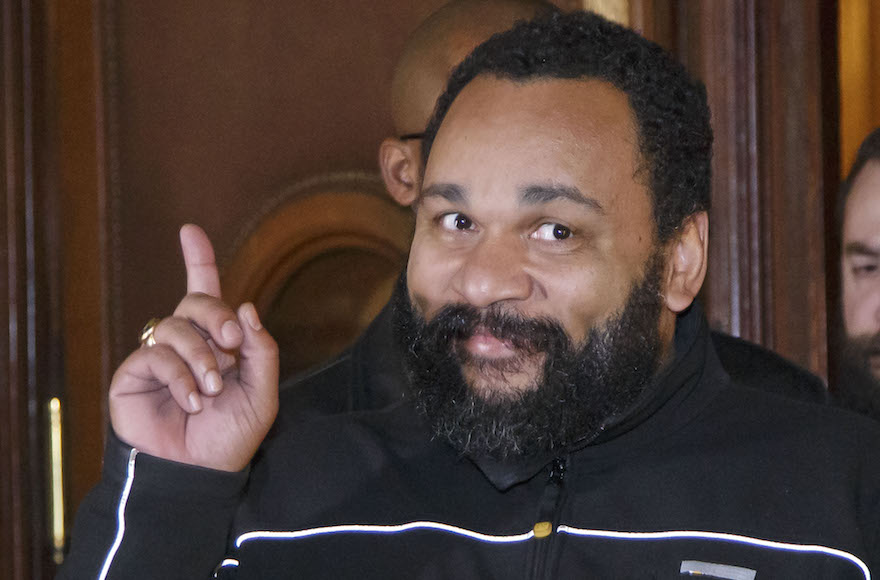 """French comedian Dieudonne M'Bala M'Bala gestures to the media as he leaves a Paris court house, Wednesday, Feb. 4, 2015. Controversial French comic Dieudonne has gone on trial charged with """"defending terrorism"""" in a Facebook post made after the three-day terror spree in Paris last month. He made a Facebook posting which said """"I feel like Charlie Coulibaly."""" The post, which has since been taken down, merges the names of Charlie Hebdo, the satirical magazine where two gunmen killed 12 people, and that of Amedy Coulibaly, who prosecutors say killed four hostages at a kosher supermarket and a policewoman. (AP Photo/Michel Euler)"""