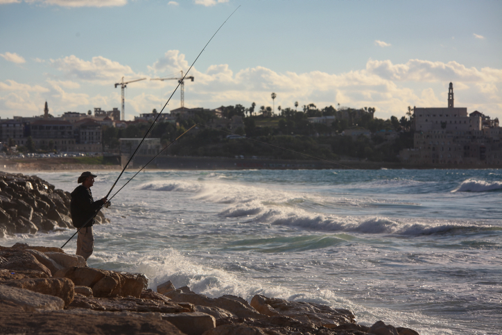 A man fishes off the coast of Tel Aviv. December 3, 2015. (Esther Rubyan/Flash90)