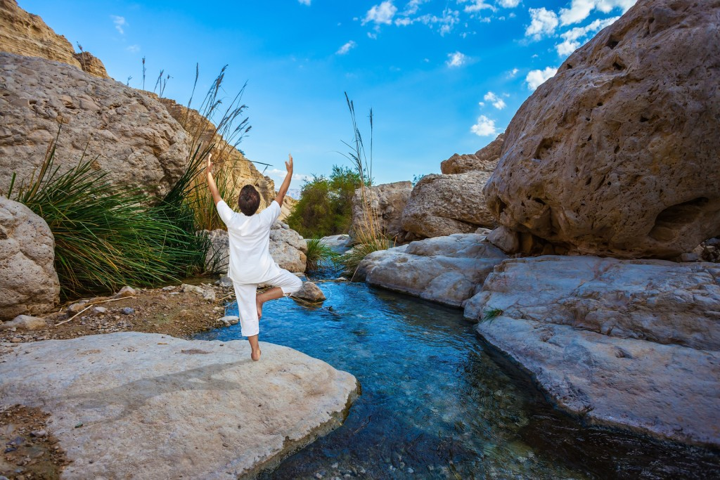 Elderly woman practices yoga on small lake in Ein Gedi
