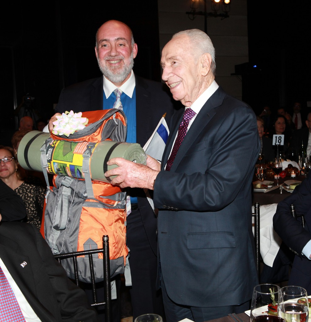 Ambassador Ron Prosor presenting Shimon Peres with a backpack.