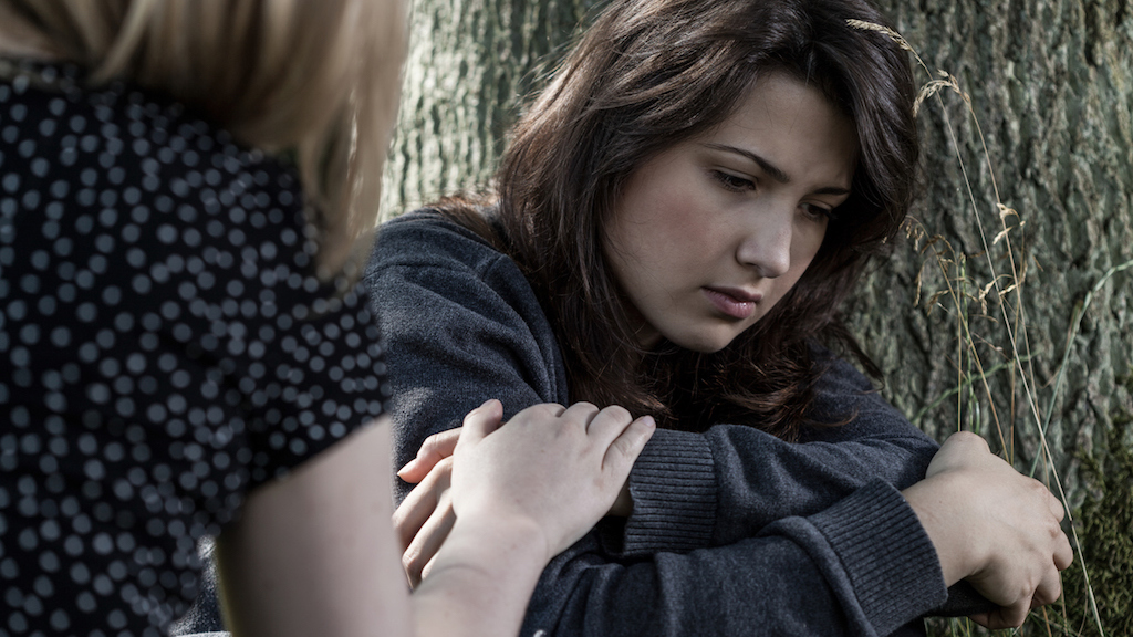 Horizontal view of a woman comforting her sad friend