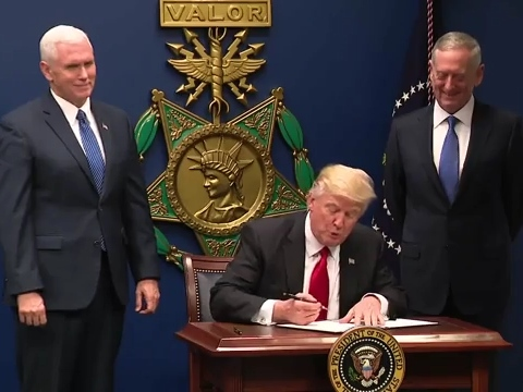Donald Trump signing the order in front of a large replica of a USAF Medal of Honor, with Mike Pence and James Mattis at his side (Public domain)