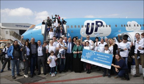 Ukrainian Jews wave Israeli flags as they pose for a group photo in front of the jet that brought them to Tel Aviv's Ben Gurion Airport in March 2017. Photo: Olivier Fitoussi / IFCJ