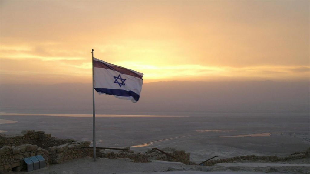 Flag of Israel atop a hill, as sunrise peaks through the clouds.