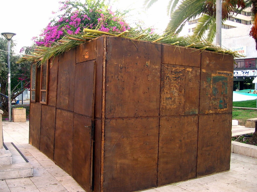 A sukkah with a palm-branch roof in Herzliya. [Photo: RonAlmog, (Flickr page) via Wikimedia Commons]