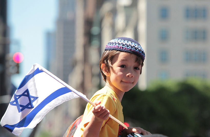 A boy wearing a kippah (Jewish skullcap) holds an Israeli flag, celebrating his pride in the Jewish State.