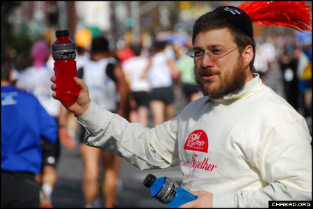 Higher POWERade: Rabbi Zev Wineberg hands out kosher sports drinks during the Marathon. (Photo by Yosef Lewis | Chabad.org)