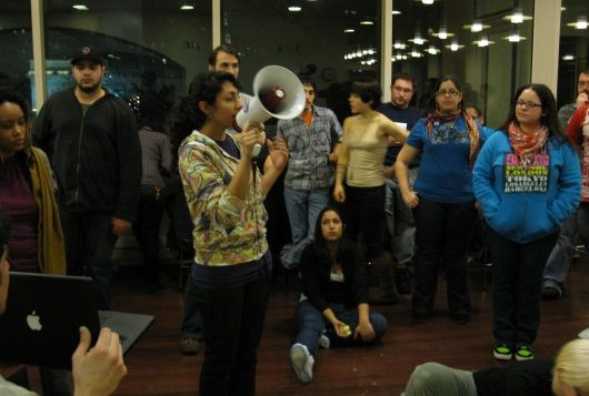 Protestor Farah Khimji addressed the crowd of students with her in the Kimmel Center cafeteria last week. At one point more than
