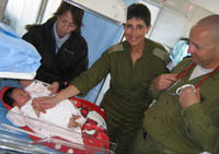 Israeli medical personnel check on a baby near disaster area in Japan check. IDF Photo