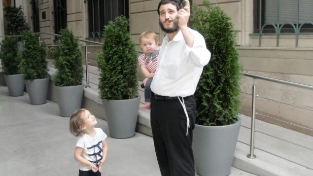 Rabbi Yisroel Kugel gets in some shofar practice with daughters Musia, left, and Sara.