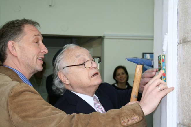 Ambassador Yehuda Avner affixes a mezuza to the front door of The Times of Israel offices in Jerusalem. (photo credit: Amanda Borschel-Dan/The Times of Israel)