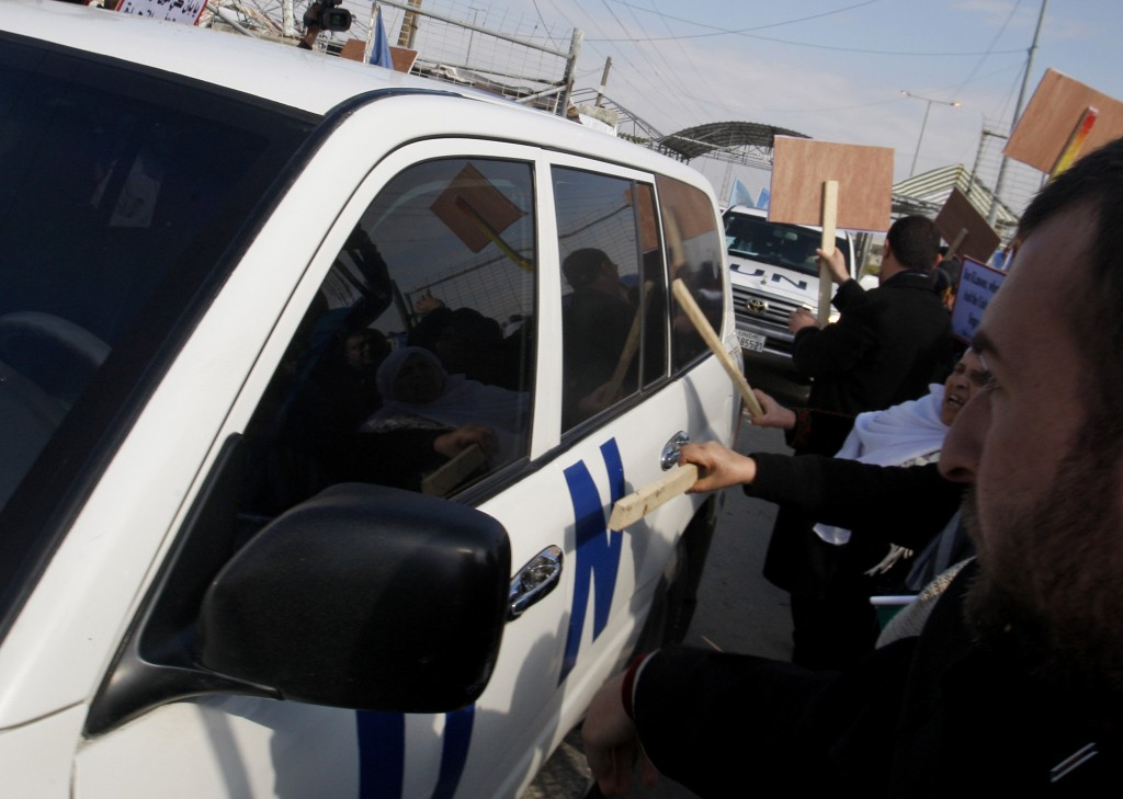 Palestinian demonstrators use sticks to hit one of the vehicles in the convoy of U.N. Secretary-General Ban Ki-moon as it enters the Erez border crossing between Israel and Gaza (photo credit: AP/Hatem Moussa)