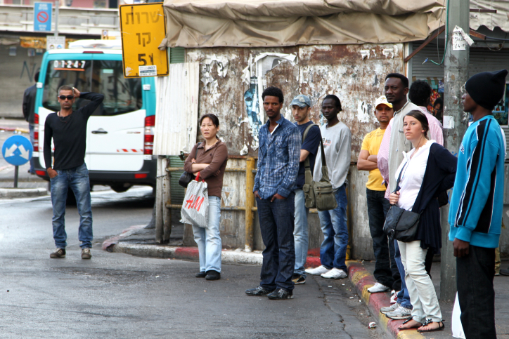 A spectrum of Israeli society including Israelis, refugees, and migrant workers, stand at a bus stop in South Tel Aviv. May 12 2011. (Photo by Nicky Kelvin/Flash90)
