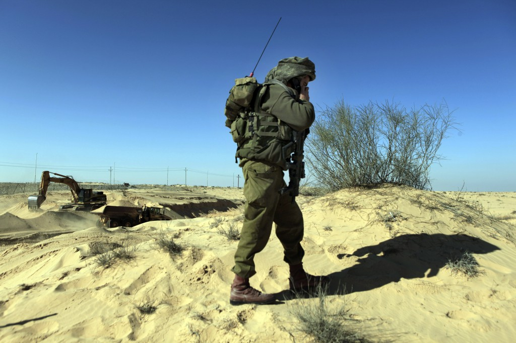 An IDF soldier secures works on the Israeli Egyptian border fence (photo credit: Tsafrir Abayov/Flash90)