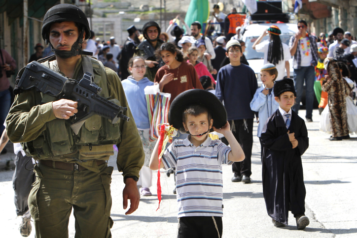 Soldiers guard Purim celebrants in the West Bank city of Hebron (photo credit: Miriam Alster/Flash90)