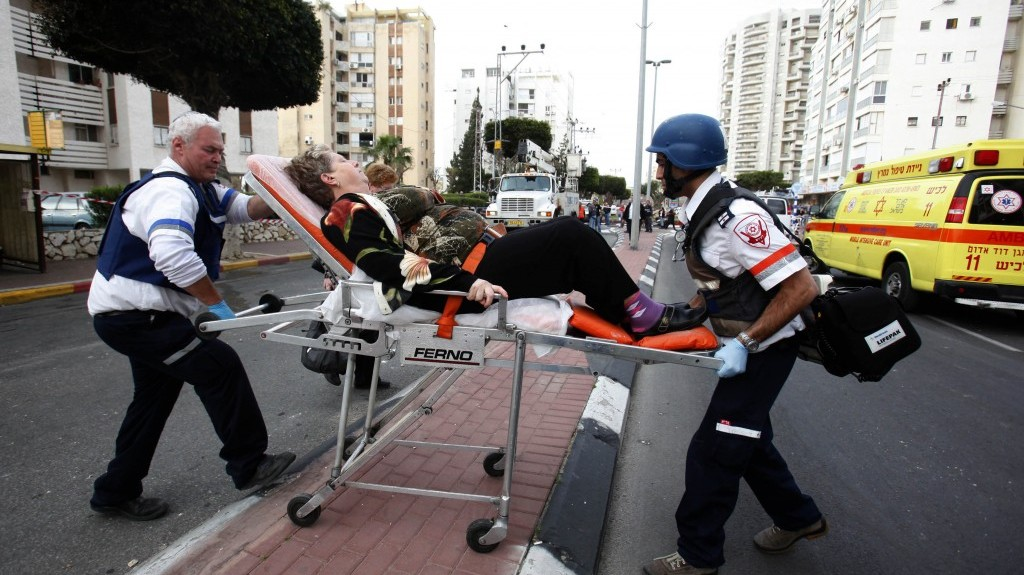 Israeli rescue personnel care for a woman injured when a grad rocket from the Gaza Strip hit Ashdod on Monday. (photo credit: Flash90)