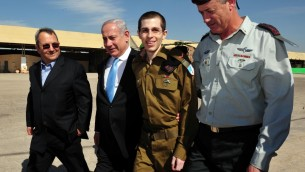 Gilad Shalit, second right, walks with Prime Minister Benjamin Netanyahu, second left, Defense Minister Ehud Barak, left, and Chief of Staff Lt. Gen. Benny Gantz, right, at the Tel Nof Air base in southern Israel, Tuesday, Oct. 18, 2011. Shalit returned home that day from more than five years of captivity in the Gaza Strip. (photo credit: Ariel Hermoni/ Defense Ministry /Flash90)