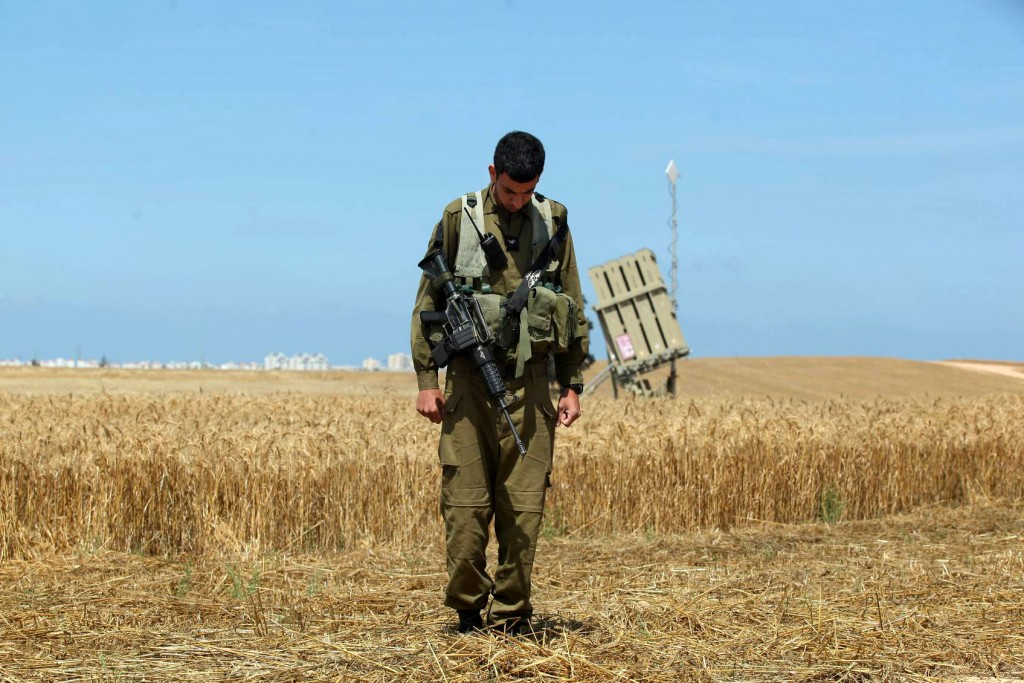A soldier, standing near an Iron Dome battery in Ashkelon, observes a two-minute silence commemorating fallen soldiers and victims of terror during Memorial Day in 2011 (photo credit: Edi Israel/Flash90)