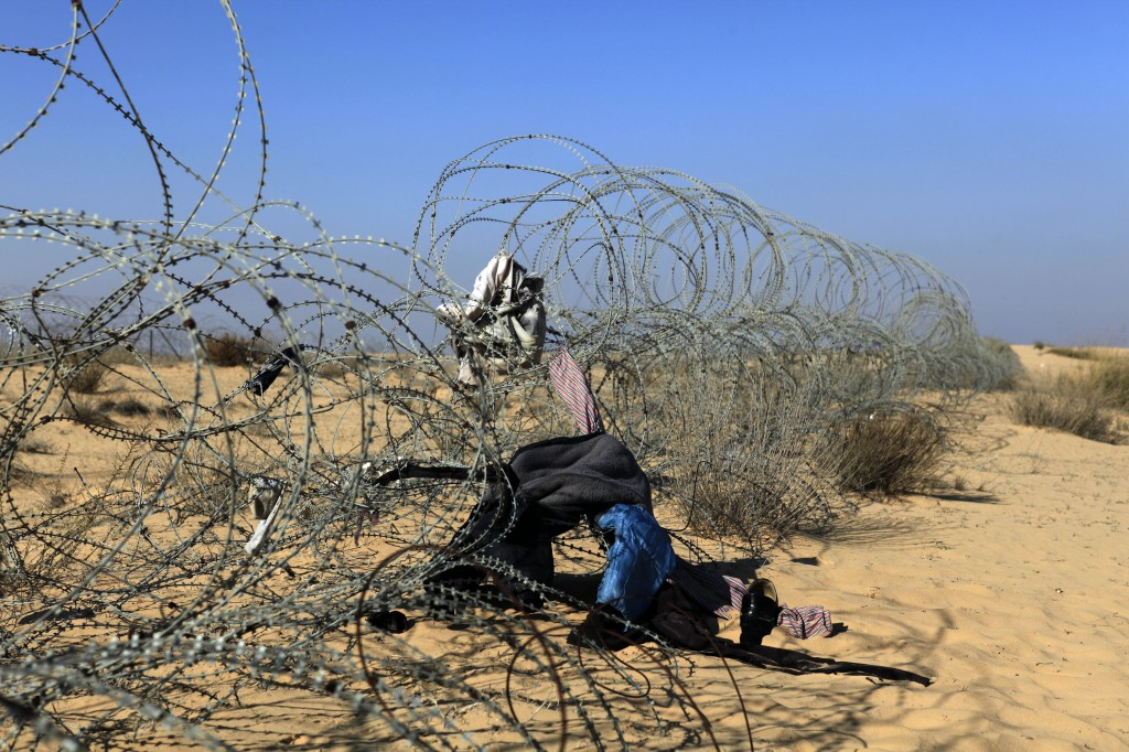 The border fence between Israel and Egypt is littered with clothing items left behind during an migrant crossing (photo credit: Tsafrir Abayov/Flash90)