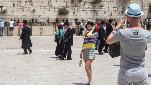 Tourists are photographed in front of the Western Wall in Jerusalem's Old City in May 2012. (photo credit: Uri Lenz / Flash 90)