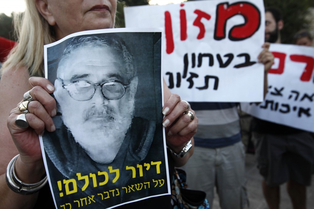 Symbol of a revolution? Social justice protesters chant slogans as they hold up pictures of Moshe Silman, who set himself on fire during a social justice demonstration in Tel Aviv (photo credit: Miriam Alster/Flash90)