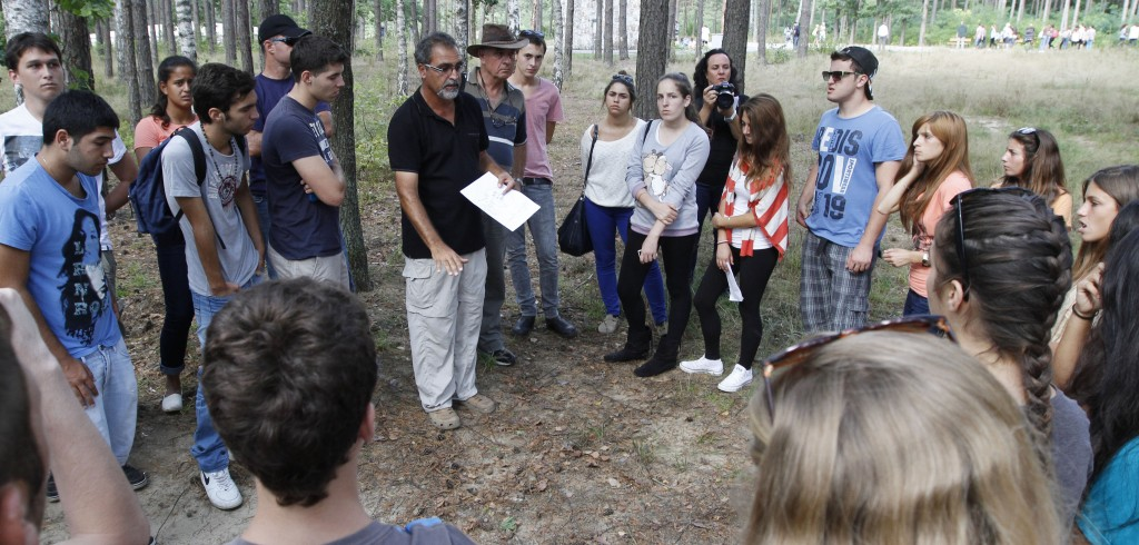 Archaeologist Yoram Haimi talking to young people from the Dror School in Israel about his findings at the site of the former German Nazi death camp of Sobibor, in eastern Poland, on Tuesday, Aug. 21 (photo credit: AP/Czarek Sokolowski)