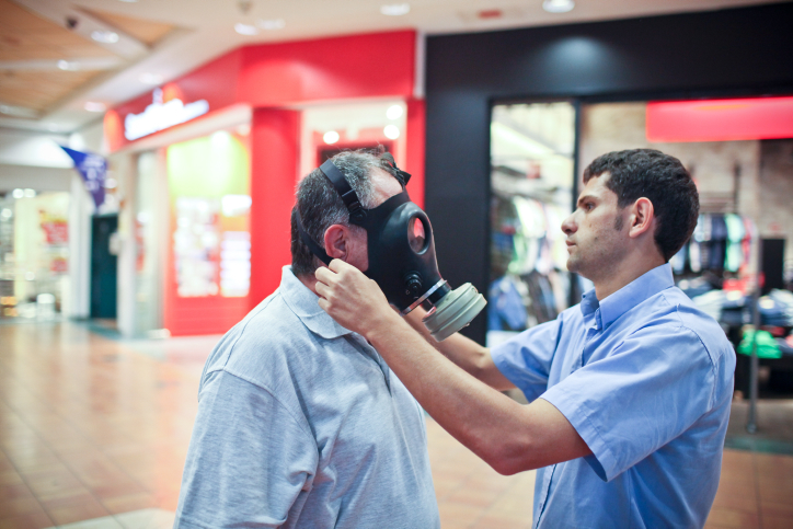A man tries on a gas mask at a distribution center in Jerusalem, July 25 , 2012 (photo credit: Noam Moskowitz/Flash90)