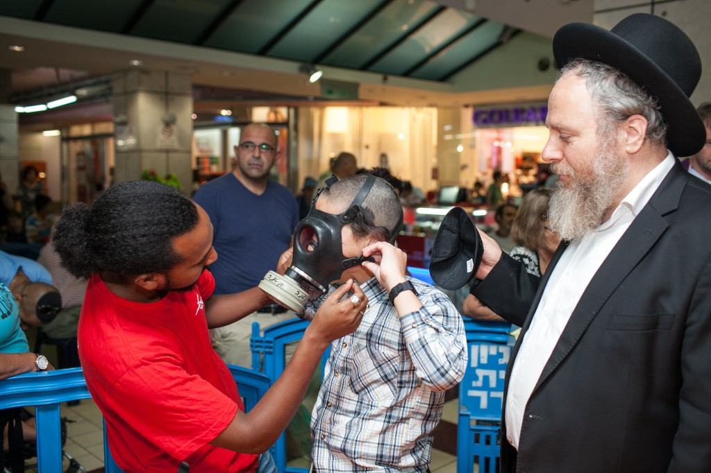 A Postal Worker Helps A Child Try On A Gas Mask In Jerusalem Photo