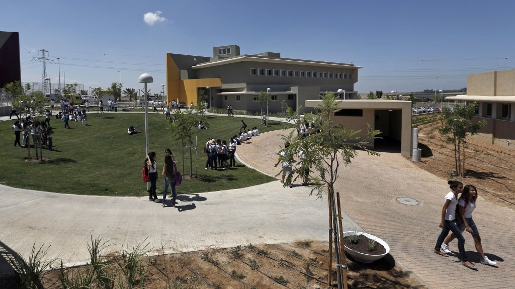 Israeli high-school students walk through the yard next to a new rocket-proof school building in the Shaar Hanegev Regional Council (photo credit: AP/Tsafrir Abayov/File)