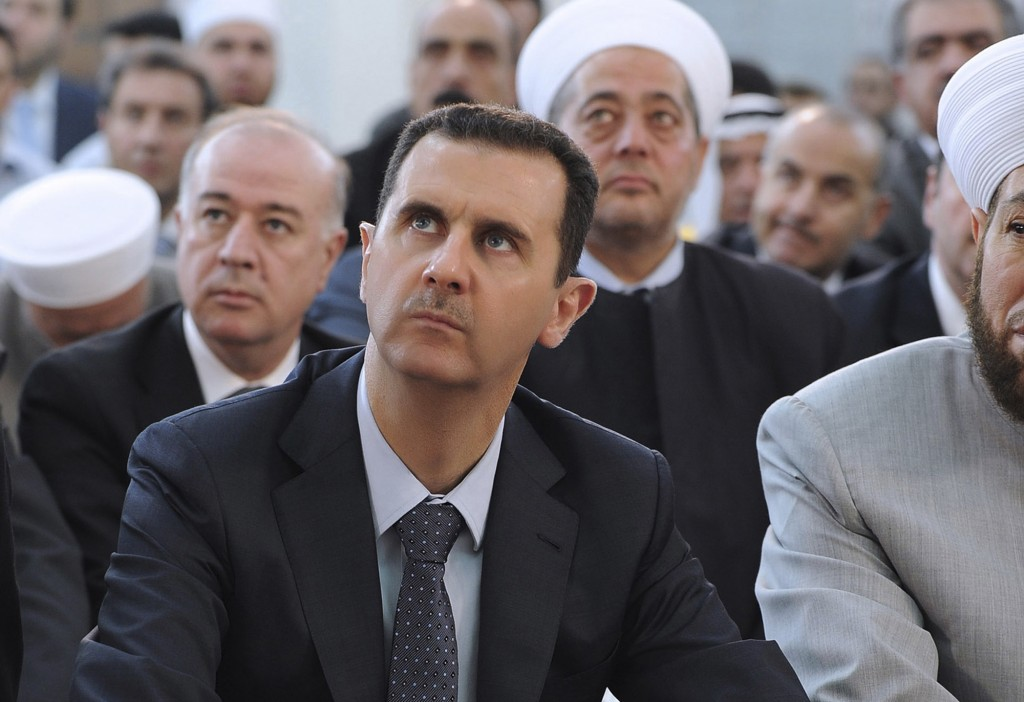 Looking for the exit? Syrian President Bashar Assad performs Eid prayers in the Hamad Mosque in Damascus, August 19 (photo credit: AP Photo/SANA)