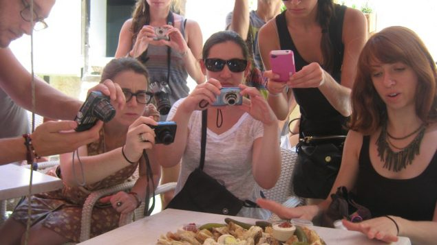 Birthright culinary tour members take photos of the fare at Jerusalem's Mahane Yehuda market. Amy Spiro