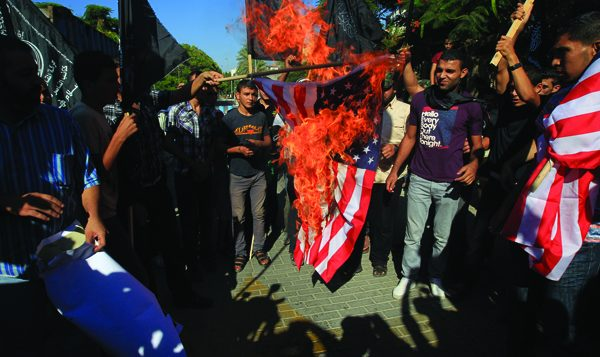 Palestinians burn an American flag at UN headquarters in Gaza City in protest against anti-Islam film. Photos by Getty Images