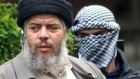 Muslim cleric Abu Hamza al-Masri, as he arrives with a masked bodyguard, right, to conduct Friday prayers in the street outside the closed Finsbury Park Mosque in London. (photo credit: AP/Max Nash, File )