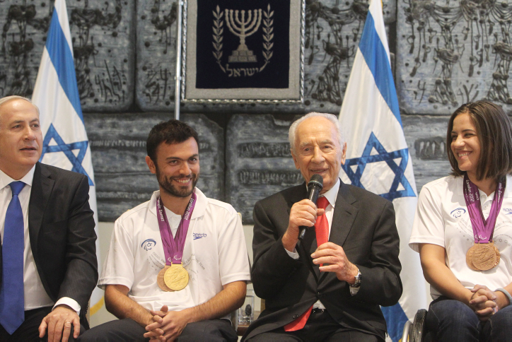 Medalists Noam Gershony (gold, tennis) and Inbal Pezaro (bronze, swimming) with President Shimon Peres and Prime Minister Benjamin Netanyahu at a welcoming ceremony for the Israeli Paralympic team at the President's Residence in Jerusalem, (photo credit: Miriam Alster/Flash90)