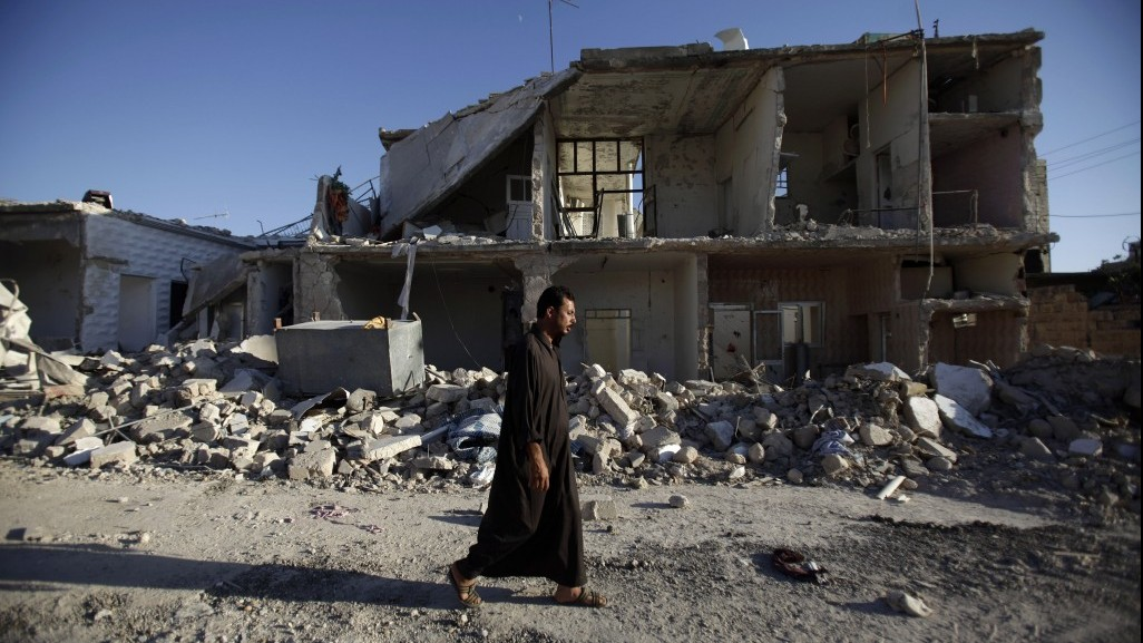 A Syrian man walks by a house destroyed in a Syrian gov