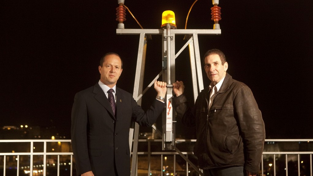 Mayor of Jerusalem Nir Barkat (L) and Director of the Israel Electric Company Yiftach Ron-Tal turned down the lights of the Old City walls in Jerusalem on Earth Day earlier this year (Photo credit: Matanya Tausig/Flash 90)