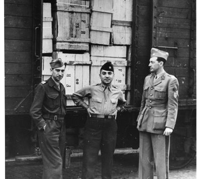 Col. Seymour Pomrenze, center, in front of train car full of items looted by the Nazis. AJHS
