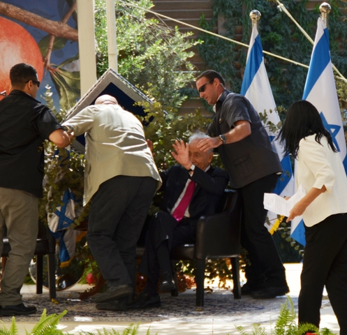 President Peres's bodyguards lifting a sign from him after it fell on him inside his sukkah on Wednesday (photo credit: Sharon Marks Altshul/The Real Jerusalem Streets)